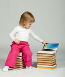 A little girl sitting among books Royalty Free Stock Photos