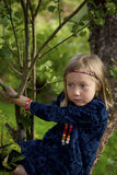 Little girl sitting on a branch of an apple tree Stock Image