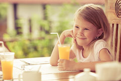 Little girl sitting at breakfast. At the day time Royalty Free Stock Images