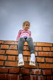 Little girl sitting on brick wall Royalty Free Stock Photos
