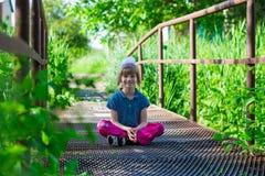 Little girl sitting on a bridge stock photo