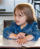 Little girl sitting in cafe Royalty Free Stock Photo