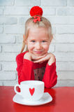 Little girl sitting in a cafe with a cup of tea Stock Image