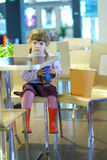 Little girl sitting at a cafe table with popcorn Royalty Free Stock Photography
