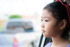 Little girl sitting in the car near the window Stock Photography