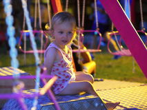 Little girl sitting on a carousel. Little girl sitting on a pink carousel at night royalty free stock image