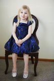 Little girl sitting in chair. Beautiful little girl wearing blue holiday christmas dress matching her blue eyes sitting in chair Stock Photos