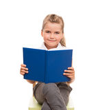 Little girl sitting on a chair with blue book and smiling Stock Photography