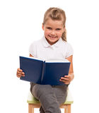 Little girl sitting on a chair with blue book and smiling. Reading is developing your intellect. You need to read more Stock Image