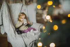 Little girl sitting on a chair with cup of tea Stock Image