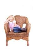 Little girl sitting on a chair Stock Photos