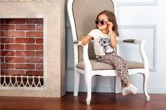 Little girl is sitting on the chair Stock Images