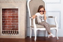 Little girl is sitting on the chair Royalty Free Stock Photography