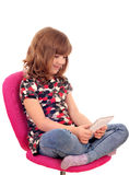 Little girl sitting on chair and play with tablet pc Royalty Free Stock Photography