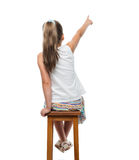 Little girl sitting on chair and pointing aside Stock Photos