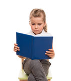 Little girl sitting on a chair and reading blue book Royalty Free Stock Image