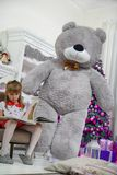 Little Girl sitting on a chair and reading a book, gave her at Christmas. Next is a large gray teddy bear and other gifts royalty free stock photo