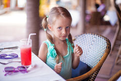 Little girl sitting in chair at restaurant waiting Stock Images