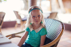 Little girl sitting in chair at restaurant waiting Royalty Free Stock Image