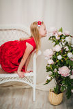 Little girl sitting on a chair and smelling a rose Stock Image