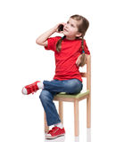 Little girl sitting on a chair and speaking by smartphone. On white background Stock Photo