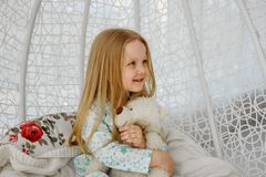 Little girl sitting in a chair suspended cocoon or in a rocking chair in a bright interior. little girl sitting in chair stock images