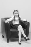A little girl is sitting on a chair. Royalty Free Stock Images