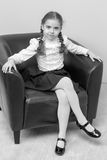 A little girl is sitting on a chair. Royalty Free Stock Image
