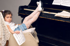Girl sitting in a chair thrown feet on the piano Stock Photography
