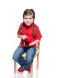 Little girl sitting on a chair and using smartphone. On white background Royalty Free Stock Image