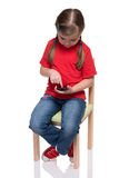 Little girl sitting on a chair and using smartphone. On white background Stock Photo