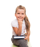 Little girl sitting on a chait with book on the knee Royalty Free Stock Image