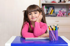 Little girl sitting in the children room at the table with color stock image