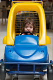 Little girl sitting in the children's machine Royalty Free Stock Photo