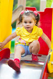 Little girl is sitting on a children's slide Royalty Free Stock Photo