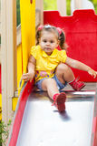 Little girl is sitting on a children's slide Royalty Free Stock Photos