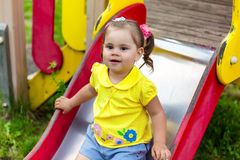 Little girl is sitting on a children's slide Stock Photo