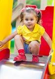 Little girl is sitting on a children's slide Stock Photography