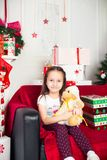 Little girl sitting on coach holding stuffed toy Stock Images