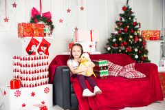 Little girl sitting on coach holding stuffed toy Stock Image