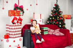 Little girl sitting on coach holding stuffed toy Royalty Free Stock Images