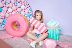 Little girl sitting in colorful room around big toyful candies, donut, lollipop Stock Photo
