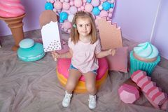Little girl sitting in colorful room around big toyful candies, donut, lollipop Stock Photography