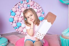 Little girl sitting in colorful room around big toyful candies, donut, lollipop Stock Images