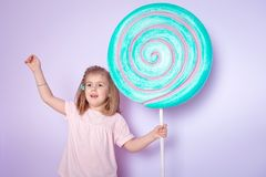 Little girl sitting in colorful room around big toyful candies, donut, lollipop Stock Photos
