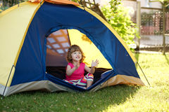 Little girl sitting in colorful tent Stock Photos