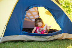 Little girl sitting in colorful tent Royalty Free Stock Photography