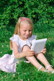 Little girl sitting with computer Stock Photos