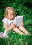 Little girl sitting with computer Royalty Free Stock Photo