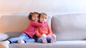 Little girl sitting on couch and crying, friend calms and embraces baby. Little blonde girl sitting on couch in living room and crying, friend sitting next and stock video